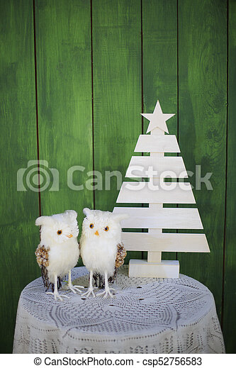Two Christmas owls on a table near a decorative Christmas tree on a green background. New year greeting card template. Christmas mock up. - csp52756583
