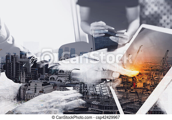 two colleague web designer discussing data and digital tablet docking keyboard and computer laptop with smart phone and design diagram on marble desk, sun light effect - csp42429967