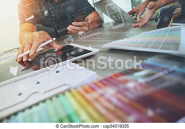 two colleagues interior designer discussing data and digital tablet and computer laptop with sample material and digital design diagram on wooden desk as concept - csp34319335
