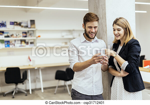 Two colleagues smiling while looking at the phone in an office - csp31712401