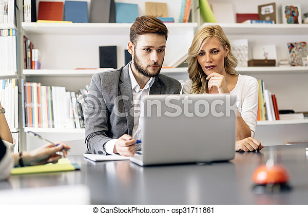Two colleagues solving problem on laptop - csp31711861