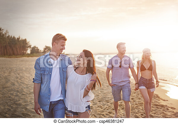 Two couples walking on the beach - csp46381247
