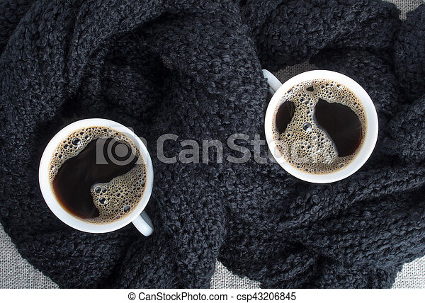 Two cups of coffee wrapped in black woolen scarf - csp43206845