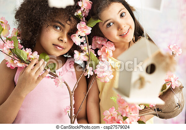 Two cute girls with pink flowers - csp27579024