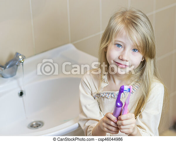 Two different toothbrushes in the girl's hands. The concept of oral care. - csp46044986