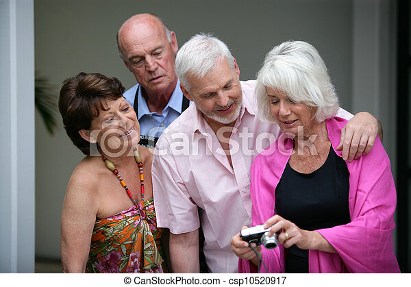 Two elderly couple looking at photos on digital camera - csp10520917