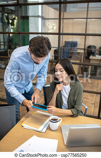 Two employees working in the office and looking involved - csp77565250