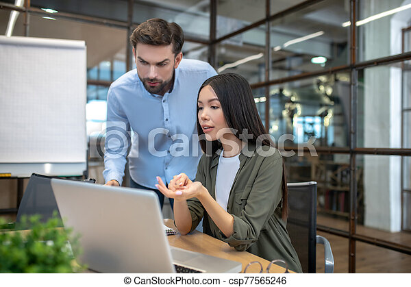 Two employees working in the office and looking interested - csp77565246
