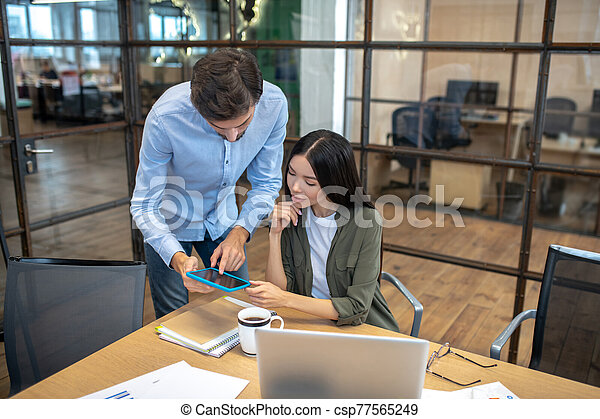 Two employees working in the office and looking concentrated - csp77565249