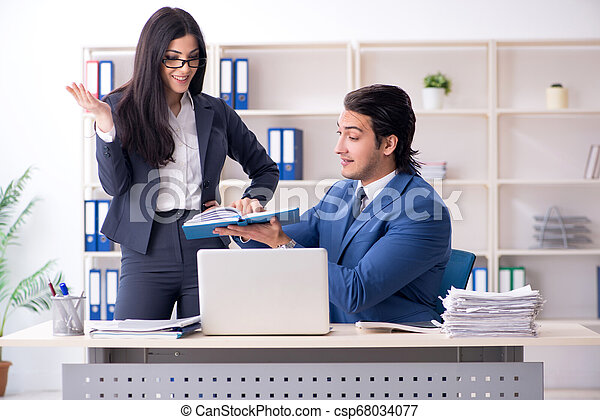 Two employees working in the office - csp68034077