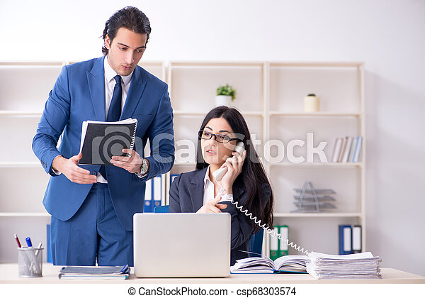Two employees working in the office - csp68303574