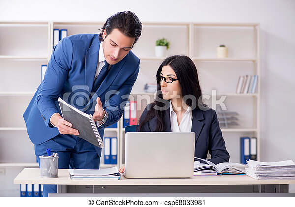 Two employees working in the office - csp68033981