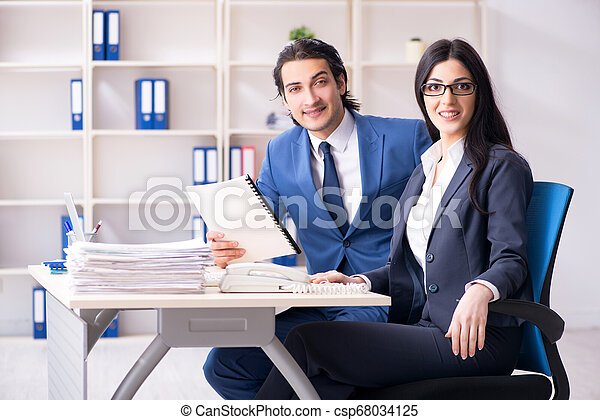 Two employees working in the office - csp68034125