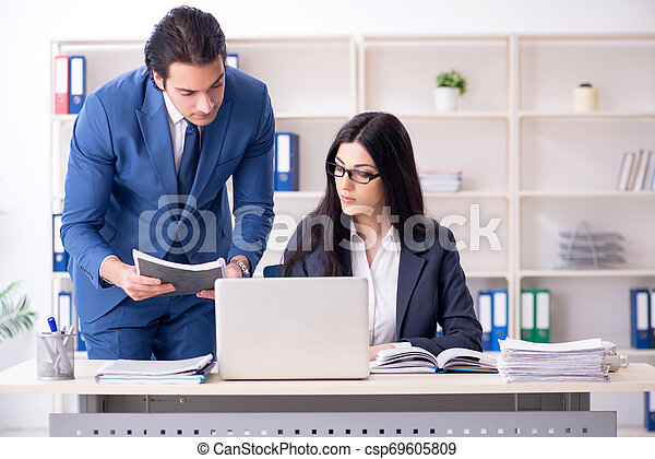 Two employees working in the office - csp69605809