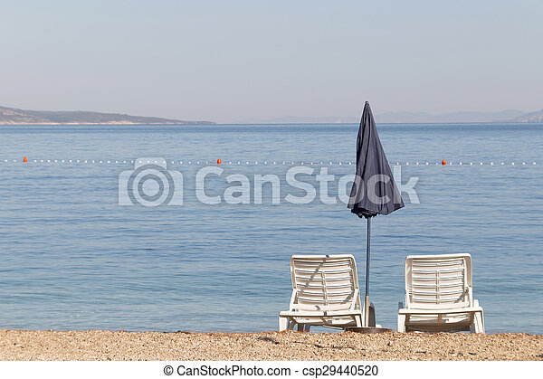 Two empty deck chair and a blue parasol - csp29440520