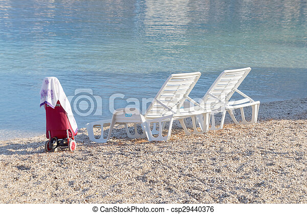 Two empty deck chair and a carrier - csp29440376