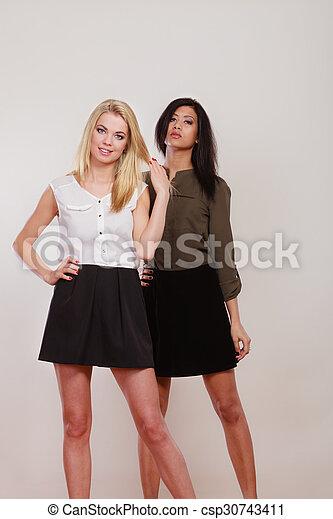two fashion women african and caucasian posing - csp30743411