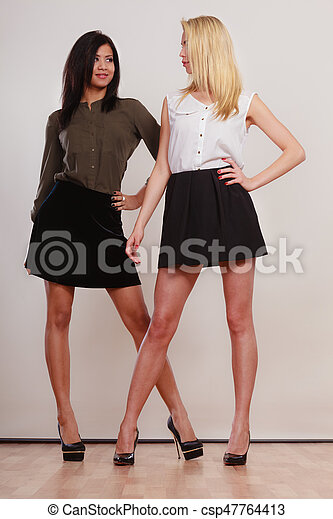 two fashion women african and caucasian posing - csp47764413