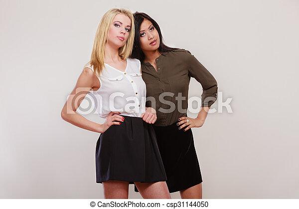 two fashion women african and caucasian posing - csp31144050