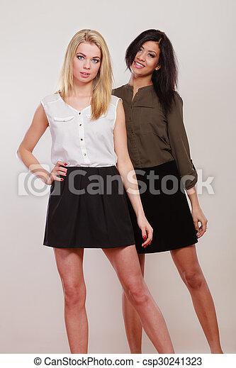 two fashion women african and caucasian posing - csp30241323