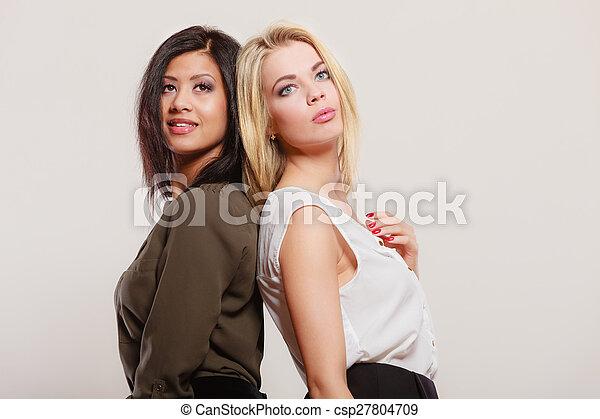two fashion women african and caucasian posing - csp27804709