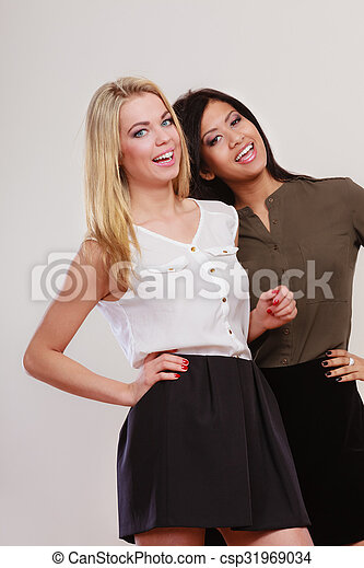 two fashion women african and caucasian posing - csp31969034