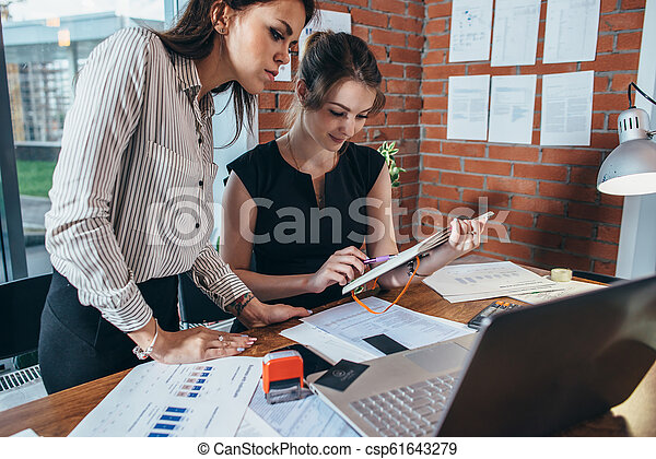 Two female colleagues in office working together. - csp61643279