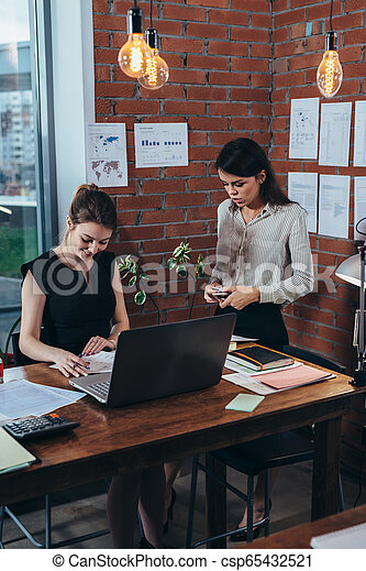 Two female colleagues in office working together. - csp65432521