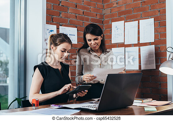 Two female colleagues in office working together. - csp65432528