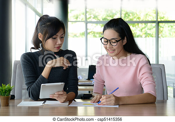 Two female colleagues working together in office - csp51415356