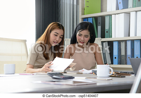Two female colleagues working together in office - csp51404407