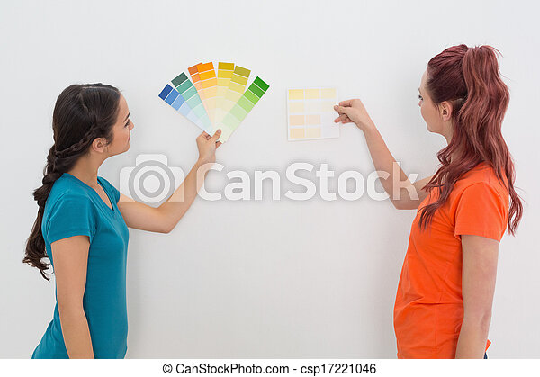 Two female friends choosing color for painting a room - csp17221046