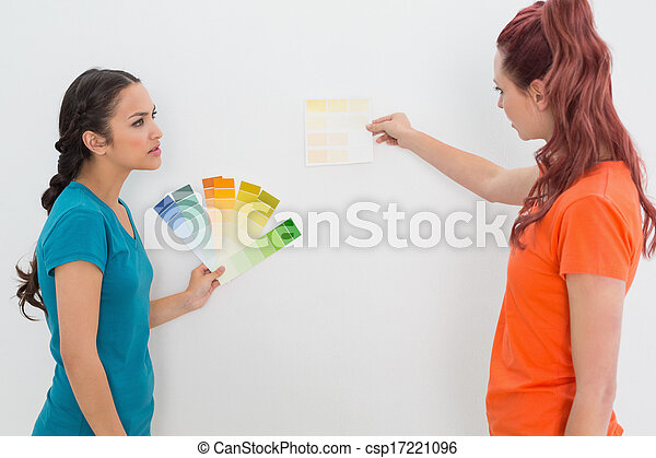 Two female friends choosing color for painting a room - csp17221096