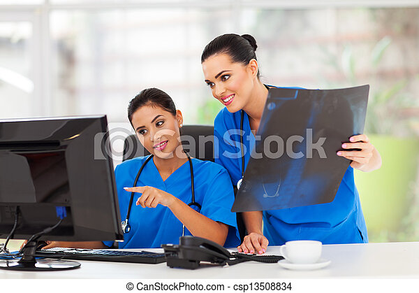 two female healthcare workers working in office - csp13508834