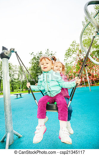Two friends on swing set of playground - csp21345117