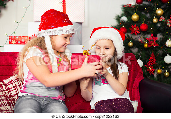 two girls in christmas costumes sitting on the couch give each other gifts tree background