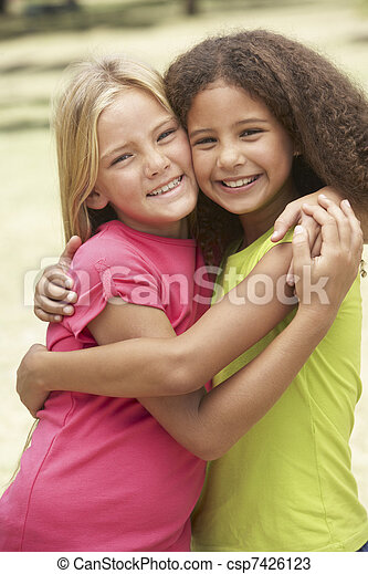 Two Girls In Park Giving Each Other Hug - csp7426123