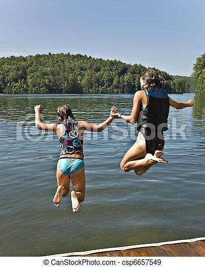 Two Girls Jumping into Lake - csp6657549