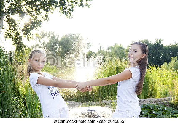 Two girls play with flowers in park - csp12045065