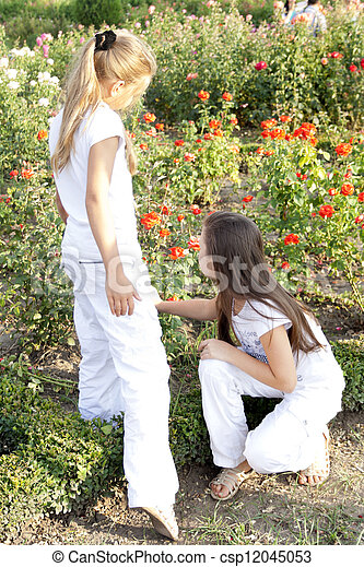 Two girls play with flowers in park - csp12045053