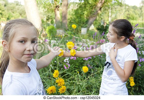 Two girls play with flowers in park - csp12045024