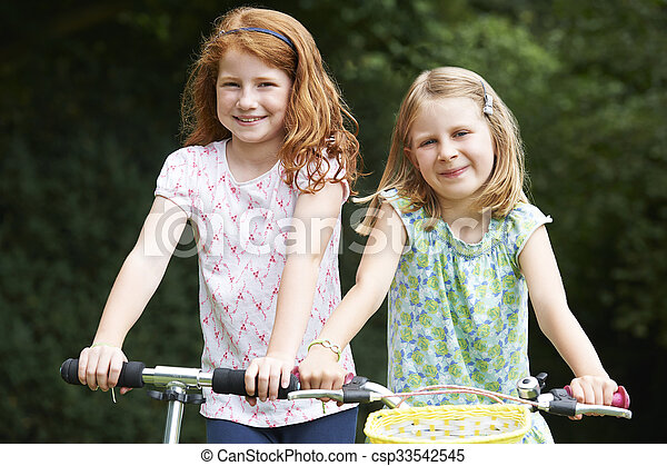 Two Girls Playing On Bike And Scooter Outdoors - csp33542545