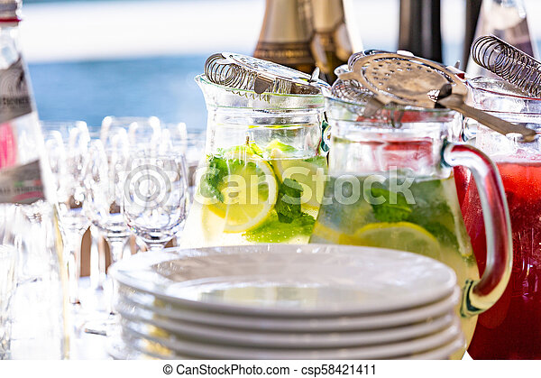 two glass jars of home made fresh raspberry lemonade or virgin mojito cocktail with a straw on the table among dishes prepared for serving - csp58421411