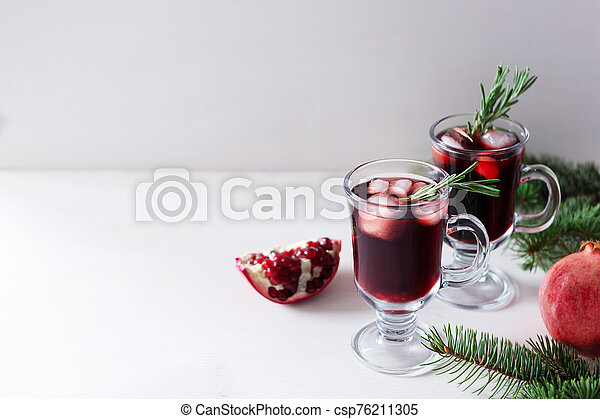 Two glass of pomegranate Christmas cocktail with champagne, soda and rosemary on a white table. Xmas drink. - csp76211305