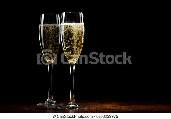 two glass with a champagne on a wooden table - csp8239975