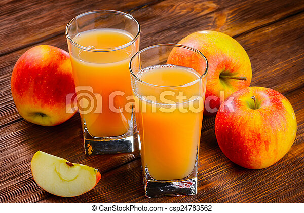 Two glasses of Apple juice and apples on wooden table. Selective focus - csp24783562