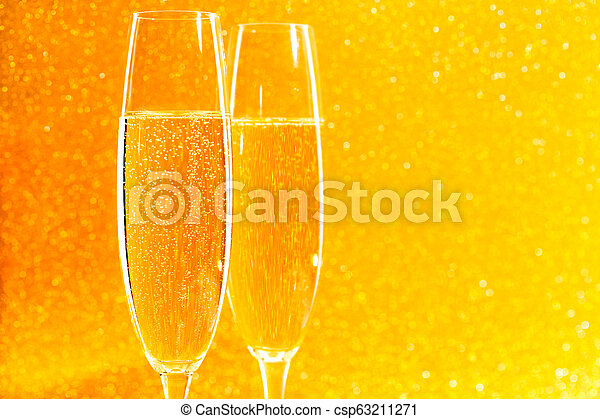 Two glasses of champagne on golden sparkling background. - csp63211271