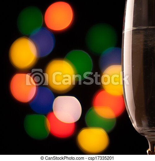 two glasses of champagne toasting against bokeh lights background - csp17335201