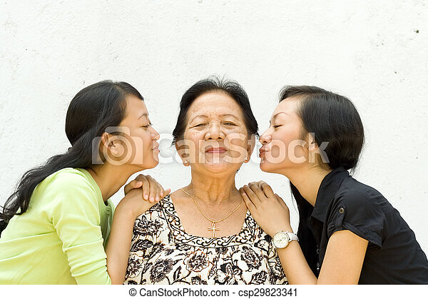 two granddaughter kiss their old grandmother - csp29823341