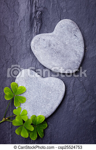 Two grey heart shaped rocks with shamrocks on a tile background - csp25524753